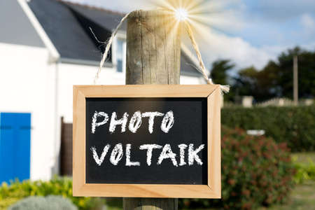 A house, sun and the photovoltaic signboard Stock Photo