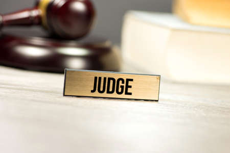 Judge gavel, law books and a sign with the imprint Judge