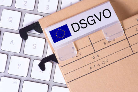 A computer and a folder with the imprint DSGVO Privacy Basic Regulation