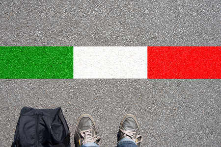A man with the suitcase is on the border with Italy