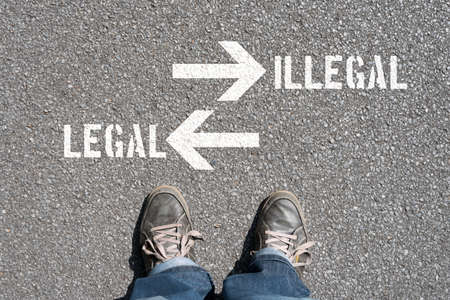 A man faces the decision Legal or Illegal Stockfoto