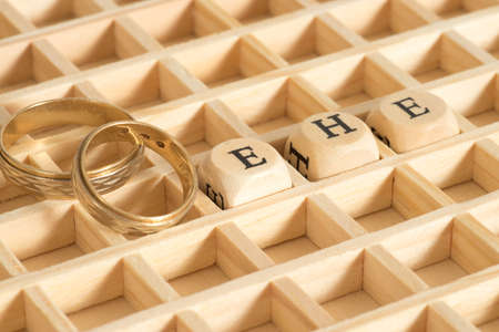 Two wedding rings and the word marriage made from Holuz letters Stock Photo