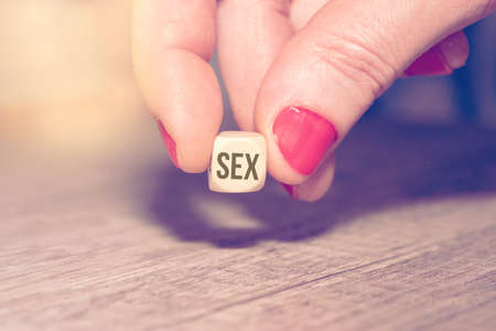 A woman and a dice with the word sex