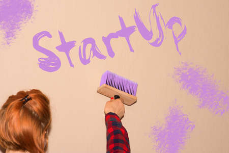 A woman strokes the wall on the word StartUp is visible Imagens