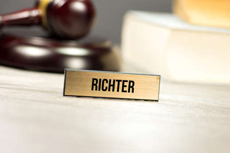 A gavel, law books and a table stand with the imprint Richter