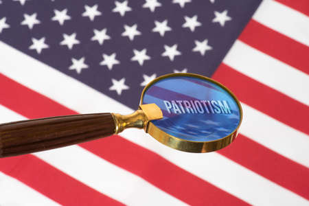 Flag of the USA, a magnifying glass and patriotism Фото со стока