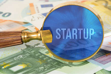 Euro bills, a magnifying glass and startup Stock Photo