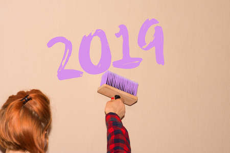 A woman paints on the wall on New Years Eve 2019