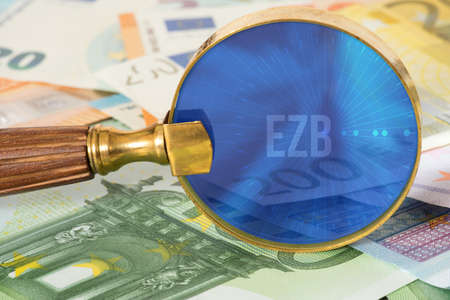 Euro banknotes, a magnifying glass and the European Central Bank ECB
