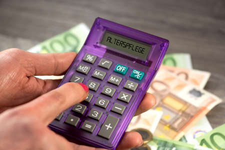 Euro banknotes, a calculator and the costs of long-term care insurance Stockfoto