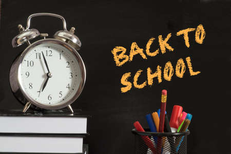 An alarm clock, books and slogan Back to School