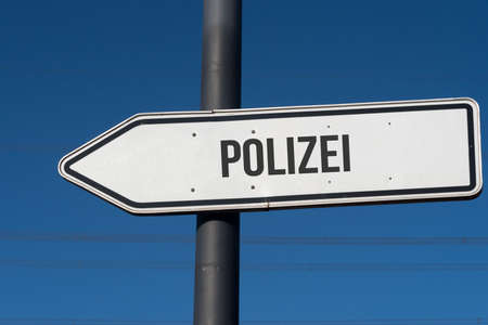 A signpost points towards the police Stock Photo