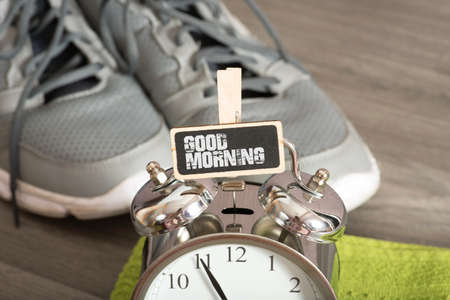 An alarm clock, sign with text Good morning, sports shoes and a towel for training