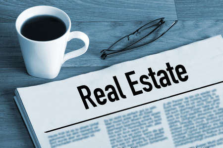 A cup of coffee, reading glasses and a newspaper called Real Estate
