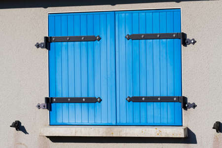 A window with blue shutters in front of it
