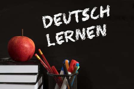 School books, apple and chalk board with the slogan German Learning Foto de archivo - 111673895