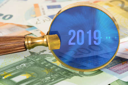 Euro banknotes, a magnifying glass and the year 2019