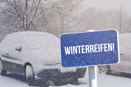 A car, snow, winter and a sign indicating winter tires Stock Photo