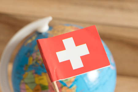 Flag of Switzerland and a globe in the background Reklamní fotografie