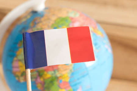 Flag of France and a globe in the background