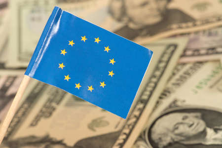 European union flag EU and dollar bills in the background Stock Photo