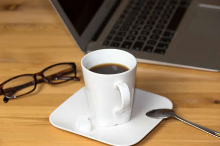 A cup of coffee, reading glasses and a computer in the office 版權商用圖片