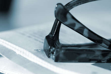 A pair of glasses and a newspaper