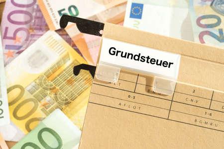 Euro-Banknoten und eine Mappe mit dem Impressum Grundsteuer