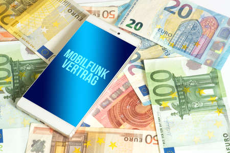 Euro banknotes, smartphone and costs for a mobile phone contract Reklamní fotografie