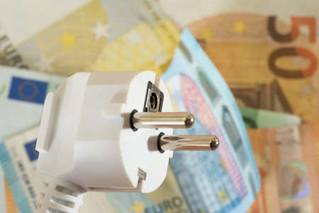 An electric plug and many euro banknotes
