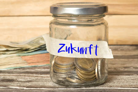 Euro coins and bills and a jar with savings for the future