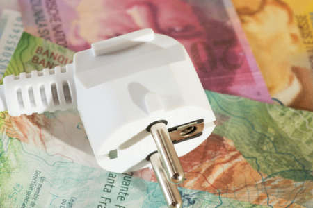 An electric plug, Swiss franc banknotes and electricity prices in Switzerland