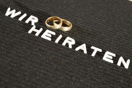 Two wedding rings and slogan We marry Stock Photo