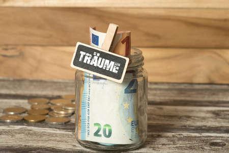 A mason jar, euro coins and saving for the dreams