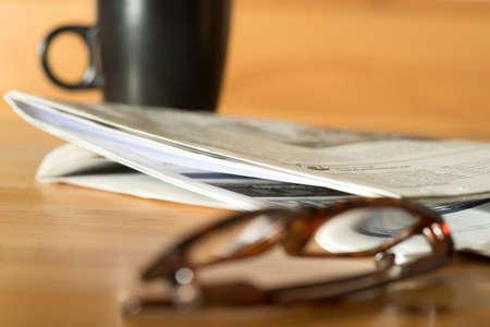 A reading glasses and a newspaper Фото со стока