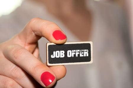 A woman is holding a sign with job offer