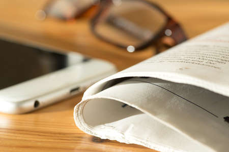 A newspaper, reading glasses and a smartphone