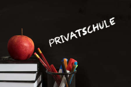 School books, pens, apple and a chalk board with the word private school