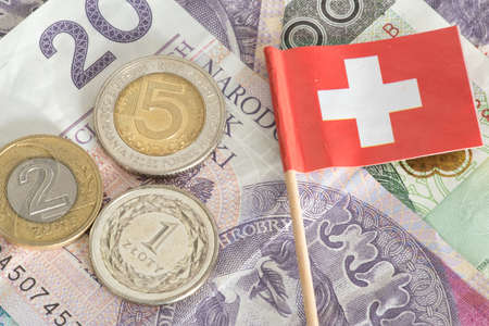 Banknotes and coins Polish zloty PLN and the flag of Switzerland Stock Photo