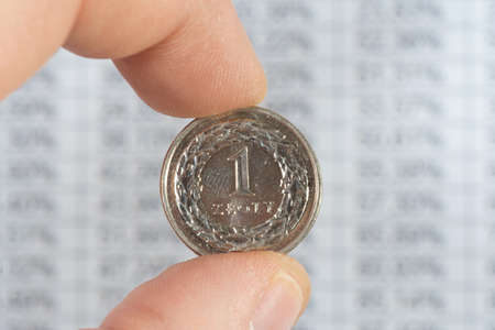 A man holds a Polish zloty PLN coin in front of a chart Reklamní fotografie