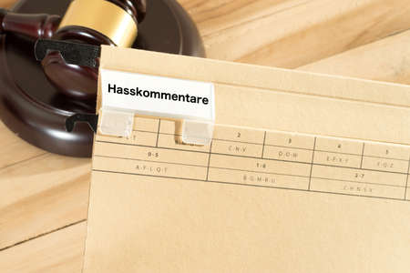 A gavel and a folder with the words hate comments Stok Fotoğraf