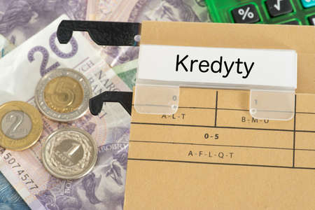 Banknotes and coins Polish zloty PLN and a folder with the word credit