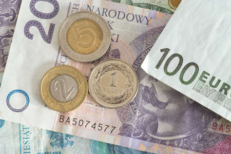 Euro bank note and banknotes and coins Polish zloty PLN