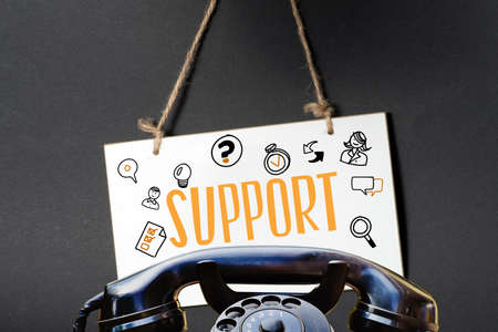 A telephone and a blackboard with the word Support