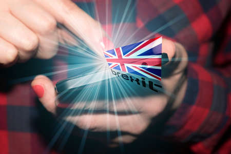 A woman with smartphone, flag of Great Britain and Brexit