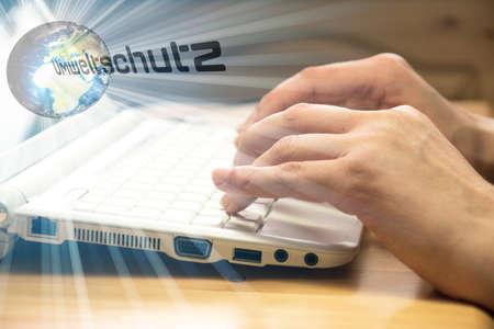 A woman at the computer, globe and environmental protection