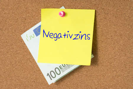 A euro bill and a note with the word negative interest