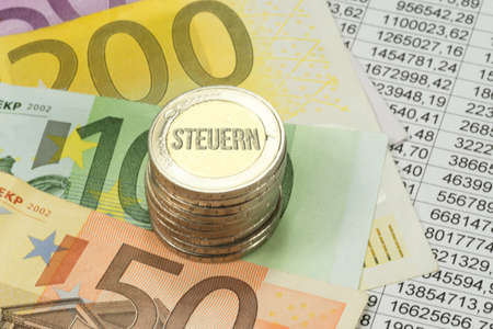 Euro coins and bills, spreadsheet and taxes Stock Photo