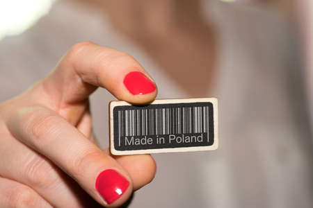 A woman and a sign with a barcode and slogan Made in Poland