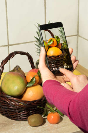 A woman photographs fresh fruits with her smartphone